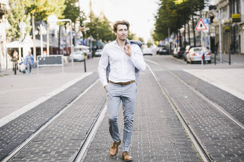 Confident man walking with hand in pocket in and jacket on shoulder in city - UUF21588