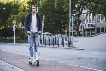 Man listening music while riding electric push scooter in city - UUF21591
