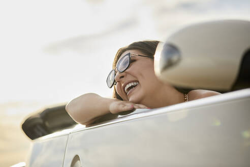 Cheerful woman laughing while sitting in convertible car for road trip - ZEDF03795