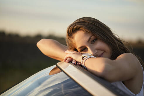 Beautiful woman leaning on car front - ZEDF03816