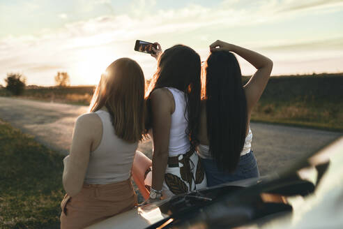 Female friends taking selfie while standing on road during sunset - ZEDF03819