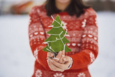 Close-up of woman holding Christmas tree with lights while standing outdoors during winter - JSCF00159