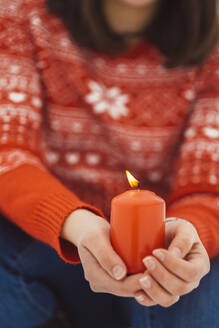 Close-up of young woman holding burning candle while sitting outdoors - JSCF00162