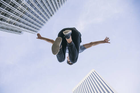 Young man performing parkour against sky in city - ABZF03331