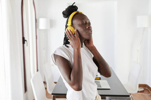 Young woman with eyes closed listening music while standing at home - KIJF03272