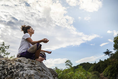 Woman meditating while sitting on rock against sky at Marmitte Dei Giganti, Marche, Italy - MCVF00621