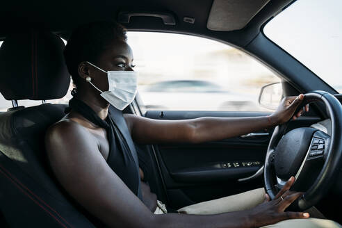 Young woman wearing face mask concentrating on driving car - MPPF01100