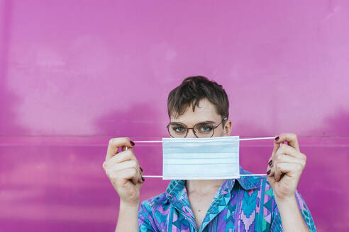 Non-binary person holding protective face mask while standing against pink wall - TCEF01153