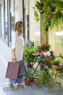 Woman carrying shopping bag while standing at flower shop - JSMF01731