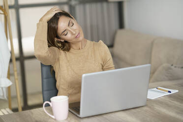 Businesswoman doing neck exercise while working on laptop at home - JSMF01740