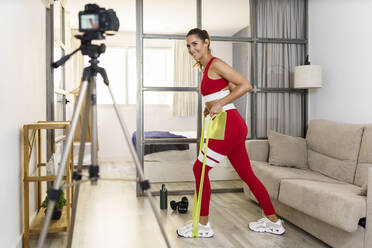 Fitness instructor recording exercise on camera at home - JSMF01752