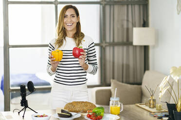 Smiling woman showing vegetable during online tutorial while standing at home - JSMF01764
