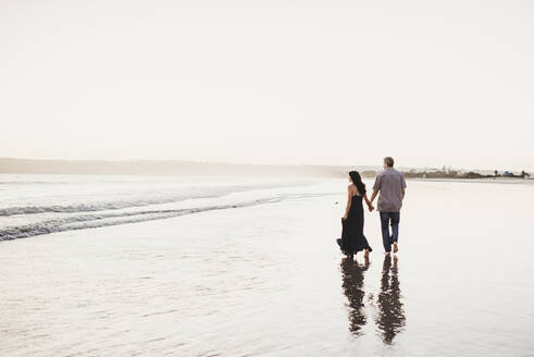 Romantic couple holding hands walking in the surf - CAVF89588