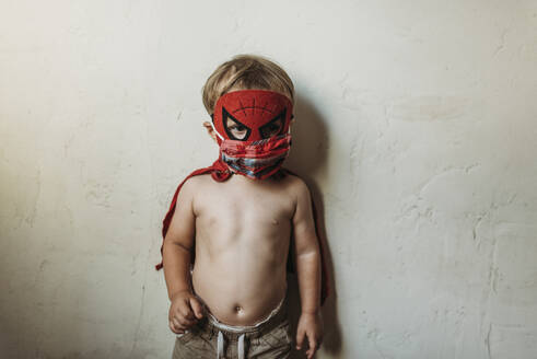 Toddler boy standing in Halloween costume and face mask - CAVF89612