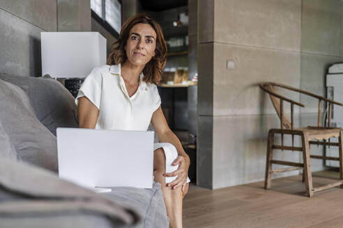 Businesswoman using laptop while sitting on laptop at office - DLTSF01229