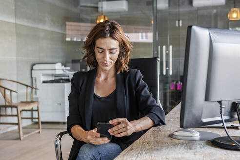 Beautiful woman using mobile phone while sitting at office - DLTSF01238