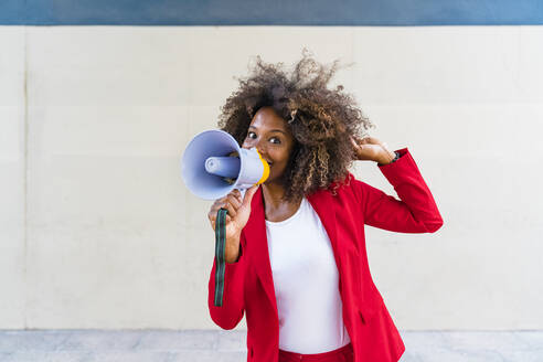 Mid adult woman using megaphone while standing against wall - MGIF00975