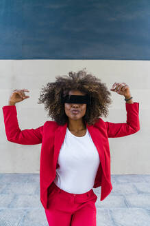 Woman with blindfold standing against wall - MGIF00984