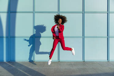Woman jumping cheerfully on sunny day - MGIF01002
