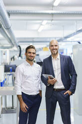 Smiling mature businessman holding digital tablet while standing by young male engineer at factory - MOEF03282
