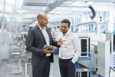 Confident businessman discussing with engineer over digital tablet at factory - MOEF03291