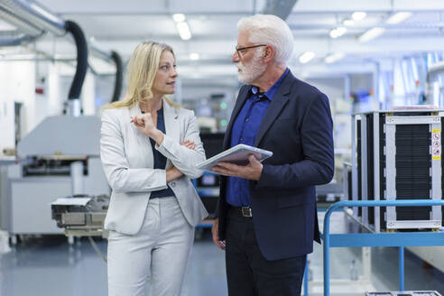 Confident businesswoman and businessman looking at each other while discussing in factory - MOEF03300