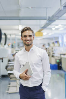 Smiling young businessman holding digital tablet while standing with hands in pockets at illuminated factory - MOEF03312