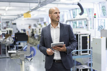 Thoughtful businessman holding digital tablet while looking away at illuminated factory - MOEF03318