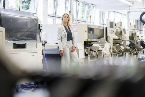 Confident mature blond businesswoman leaning on machinery at illuminated industry - MOEF03330