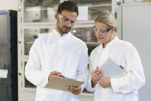 Young male technician discussing over clipboard with female blond colleague holding digital tablet at laboratory - MOEF03339