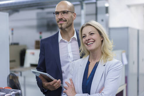 Cheerful businesswoman standing by colleague while looking away in factory - MOEF03342