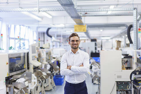 Smiling young businessman standing with arms crossed at illuminated factory - MOEF03363