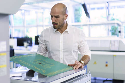 Confident mature male technician examining large circuit board at factory - MOEF03375