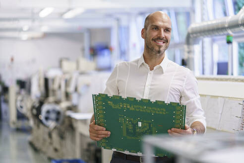 Smiling male technician holding large circuit board while looking away at factory - MOEF03381