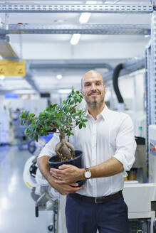 Confident male professional holding potted plant while standing at factory - MOEF03387