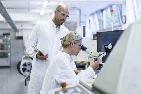 Male technician standing by female scientist looking into microscope while doing research in laboratory - MOEF03390