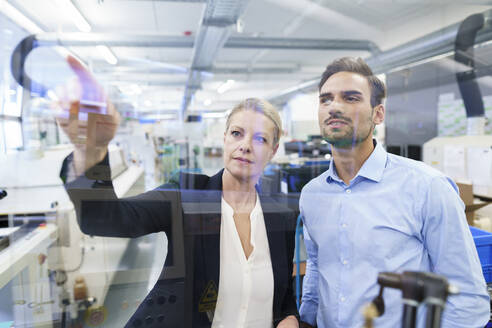 Confident businesswoman planning with young engineer while pointing at glass interface in factory - MOEF03408
