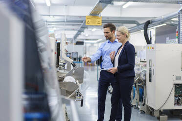 Confident young engineer discussing with businesswoman while pointing at machinery in factory - MOEF03423