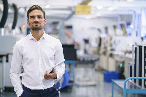 Confident young businessman holding digital tablet while standing at illuminated factory - MOEF03438