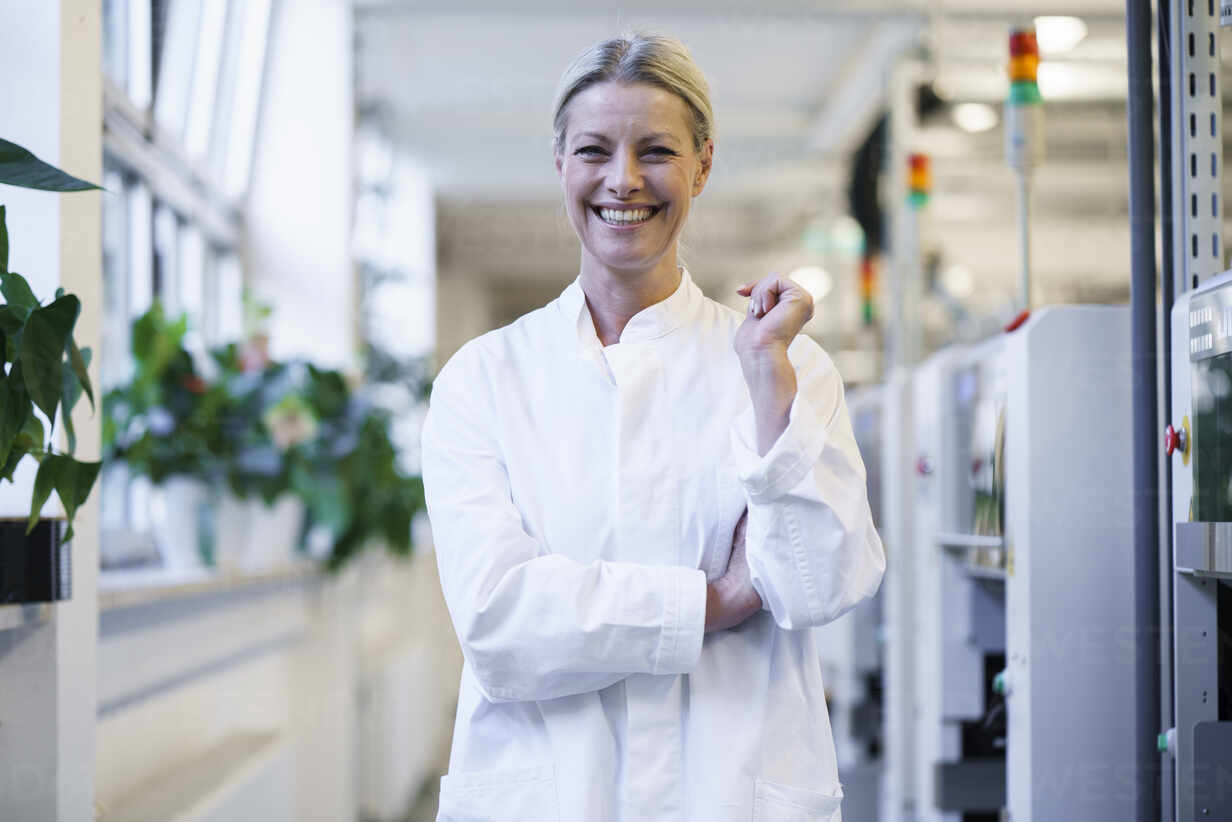 Happy mature female scientist standing by machinery at laboratory - MOEF03456 - Robijn Page/Westend61