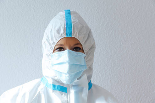 Nurse wearing protective suit and workwear while standing against  - PGF00093