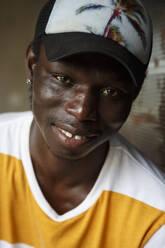 Man wearing hat smiling while sitting outdoors - NGF00664