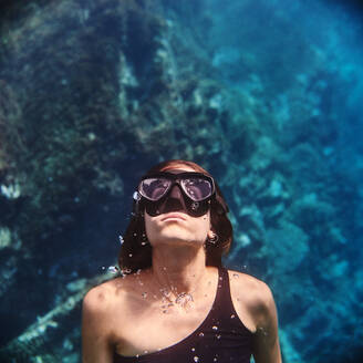 Young female diver in swimsuit and snorkeling mask floating in clean transparent sea water - ADSF15686