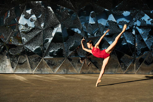Side view of graceful ballerina in pointe shoes dancing on street near glass building while balancing in split with outstretched arms - ADSF15707