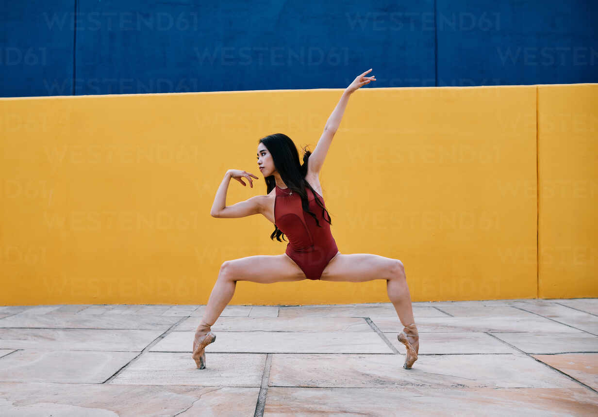 Flexible female ballet dancer performing in city near vibrant building while balancing on tiptoes in pointe shoes - ADSF15710 - ADDICTIVE STOCK CREATIVES/Westend61