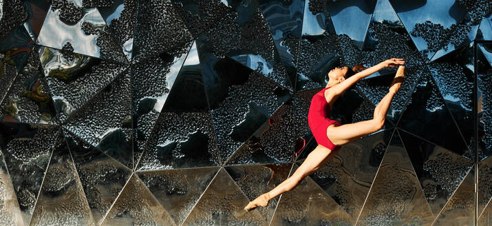 Side view of flexible ballerina dancing gracefully in urban area while jumping above ground in split and looking up - ADSF15713