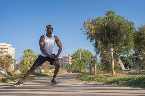 Full body of young muscular African American sportsman in headphones and sunglasses doing stretching exercise while preparing for jogging in city park in summer day - ADSF15815