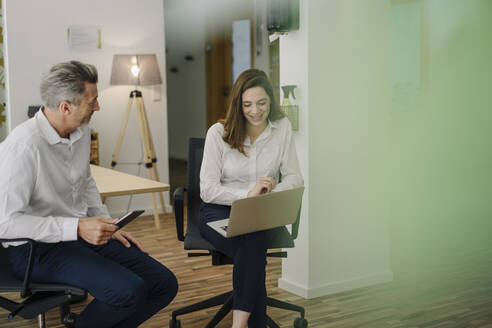 Smiling woman using laptop while sitting on chair by businessman in office - JOSEF01988