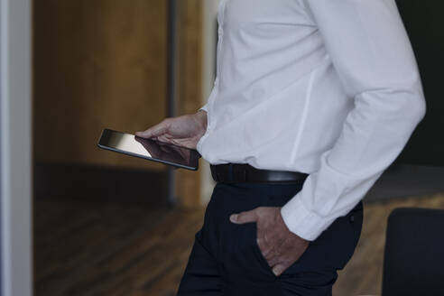 Businessman with hands in pockets holding digital tablet while standing at office - JOSEF02045