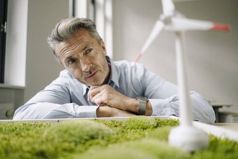 Businessman looking at wind turbine toy over moss frame while leaning on table at office - JOSEF02111